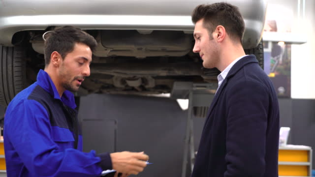 Young mechanic and custumer looking car in auto repair shop video