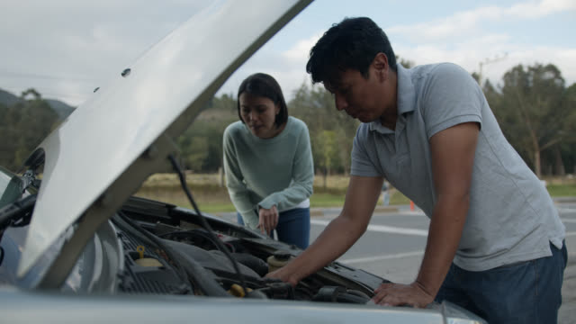 Young mechanic assisting female customer with a vehicle breakdown