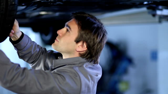 Jovem mecânico trabalhando sob car - vídeo