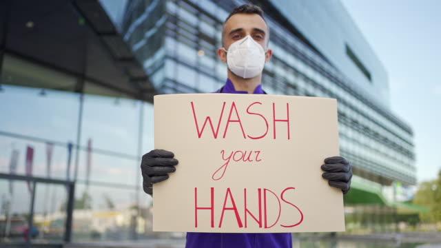 junge arzt hält eine wäsche ihre hände nachricht zeichen - wachsamkeit stock-videos und b-roll-filmmaterial