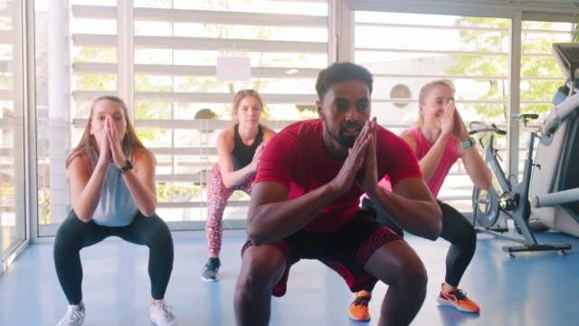 stockvideo's en b-roll-footage met jonge mannen en vrouwen die dynamische springende oefeningen doen bij gym - fitnessleraar