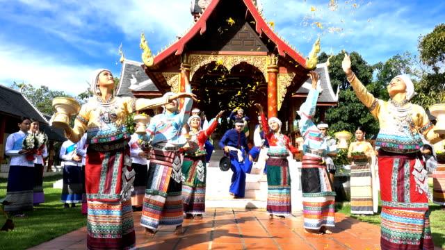 vídeos de stock, filmes e b-roll de homens e mulheres jovens usam traditionnel tailandês vestido dançando e strew orquídea flor no templo-4k - tradição