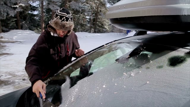 Young men Cleaning the car from the snow video