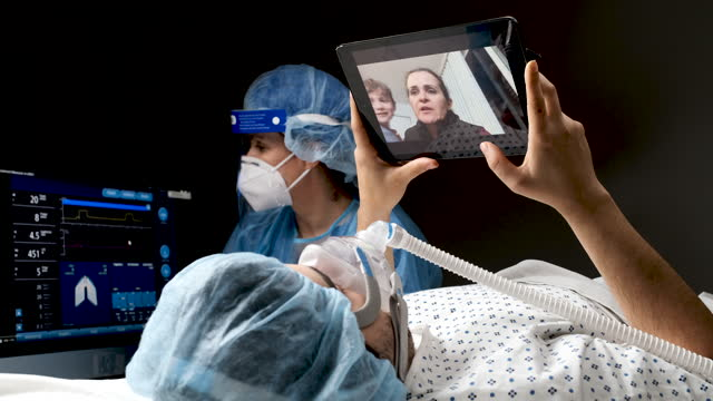 Young men connected to a ventilator talking to his family using a digital tablet