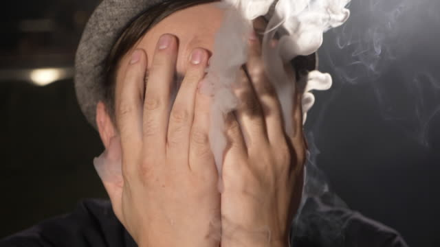 Young men covering his face by hands and exhaling lot of smoke through fingers. Young men covering his face with hands and exhaling lot of smoke through his fingers. Smoking face closeup, slow motion. smokehouse stock videos & royalty-free footage