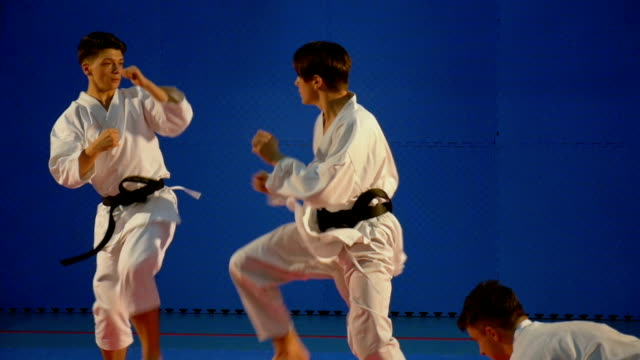 Young men fighting in karate competition in slow motion video