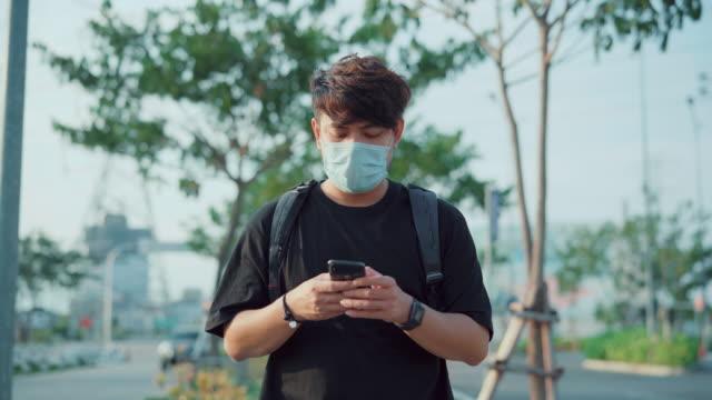 junge männer in schutzmaske mit smartphone stock video - smartphone mit corona app stock-videos und b-roll-filmmaterial