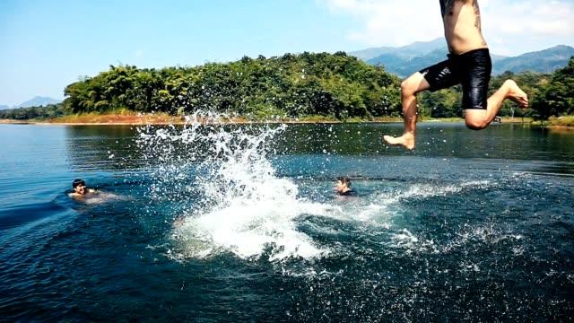 unga män hoppa från piren i sjön tillsammans, vänner hoppar från bryggan vid sjön på en solig dag - flod vatten brygga bildbanksvideor och videomaterial från bakom kulisserna
