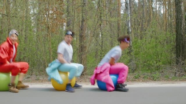 vídeos de stock, filmes e b-roll de homens novos que saltam em esferas brilhantes - humor