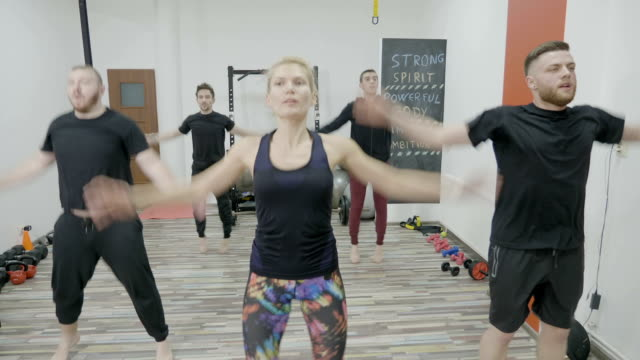 Young men on zumba class warming up by dancing in a gym studio led by a female instructor video