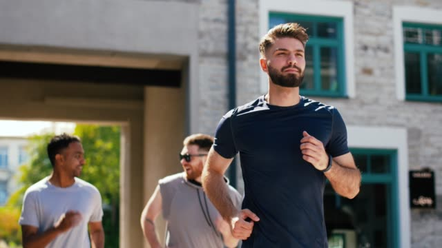 young men or male friends running outdoors - vídeo