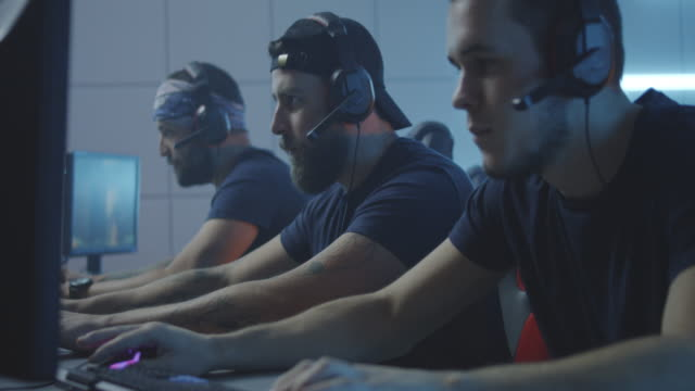 young men playing at a gaming tournament - competizione video stock e b–roll