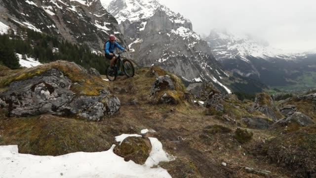 unga män rida e-mountainbikes över svåra fjällterräng - grindelwald bildbanksvideor och videomaterial från bakom kulisserna