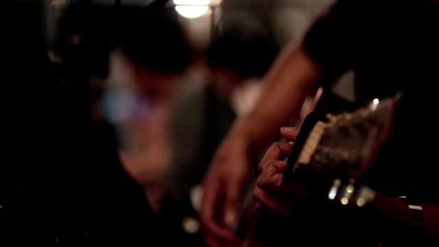 unga män sitter solo spela gitarr - gitarrist bildbanksvideor och videomaterial från bakom kulisserna