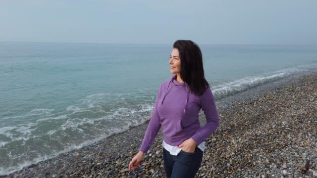 stockvideo's en b-roll-footage met jonge vrouw van middelbare leeftijd wandelen langs de kust genieten van de lente zon en het bewonderen van de natuur - bewondering