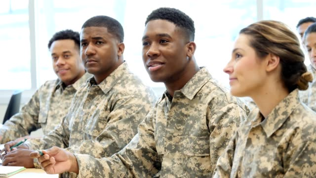 Young military soldier asks a question during class at military academy Young male soldier gestures with his pen while asking a question during a class at a military academy. He is surrounded by fellow soldiers. They are wearing camouflage clothing. military uniform stock videos & royalty-free footage
