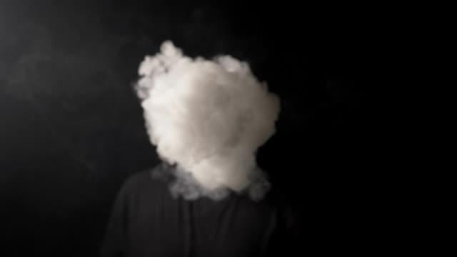 vídeos y material grabado en eventos de stock de milenario joven con barba y bigote vaping electrónico cigarrillo y soplar una gran nube de humo a la cámara en cámara lenta - soplar