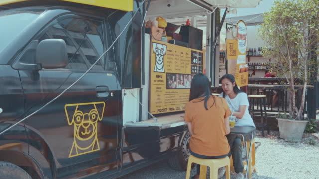 stockvideo's en b-roll-footage met jonge duizendjarige mensen kopen eten en drinken van voedsel vrachtwagen - foodtruck