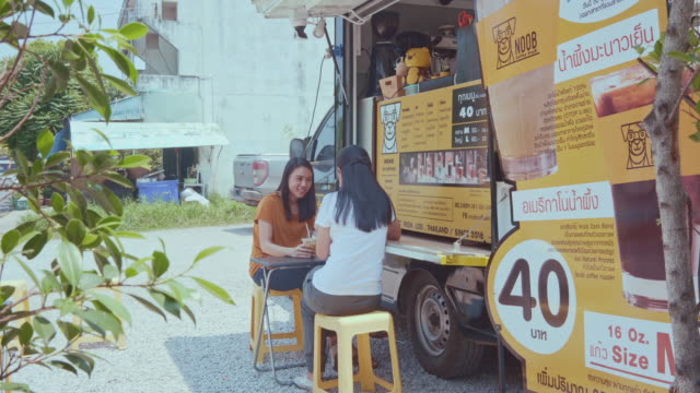 Young millennial people buying food and drink from Food Truck