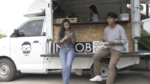 Young millennial people buying food and drink from Food Truck video