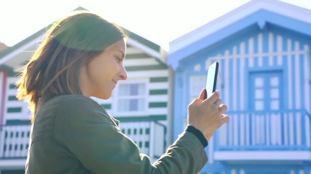 vídeos de stock e filmes b-roll de young millennial woman going on holidays and using her phone to connect and communicate with friends and family - aveiro