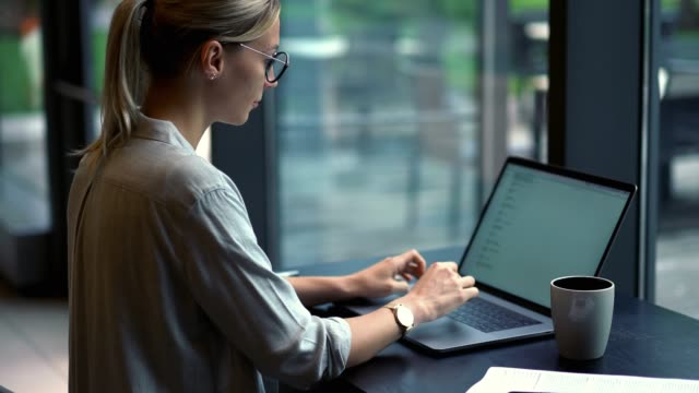 Young millennial woman typing text information for sending email to colleague via application on modern laptop computer