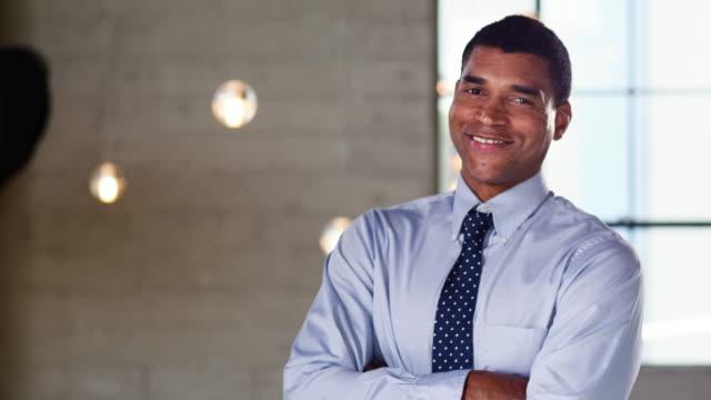 オフィスでカメラに笑顔若い混血実業家 - 上半身点の映像素材/bロール
