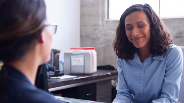 Young mixed race businesswoman talking to a female client video