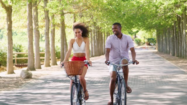 Young mixed race couple riding bicycles on a tree lined road video