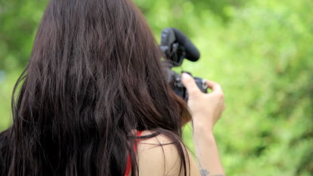 Young mixed race female indie film maker shooting in a green natural setting with grass on background video