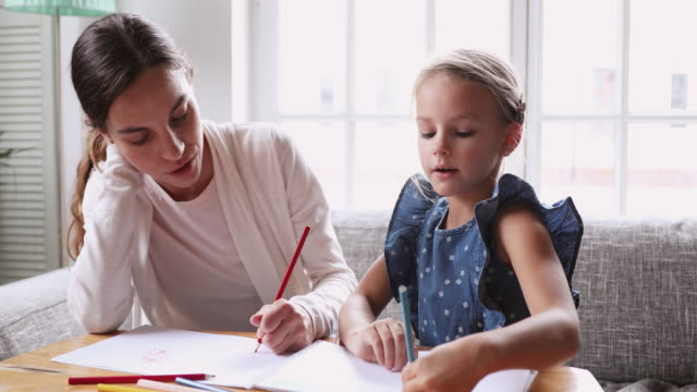 Young mixed race female tutor teaching little girl drawing.