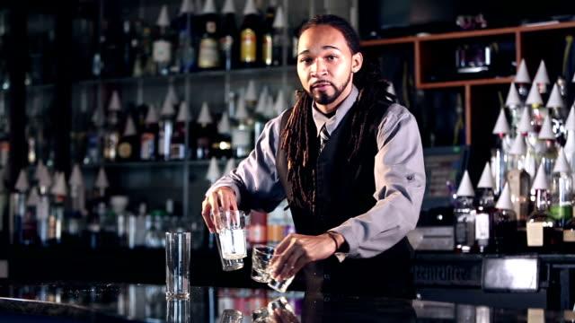 바텐더로 일 하는 젊은 혼합된 인종 사람 - bartender 스톡 비디오 및 b-롤 화면
