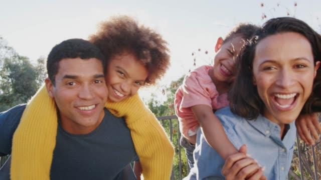 若い混合人種の両親とその子供たちは、カメラを探して庭で楽しんで、クローズアップ - 上半身点の映像素材/bロール