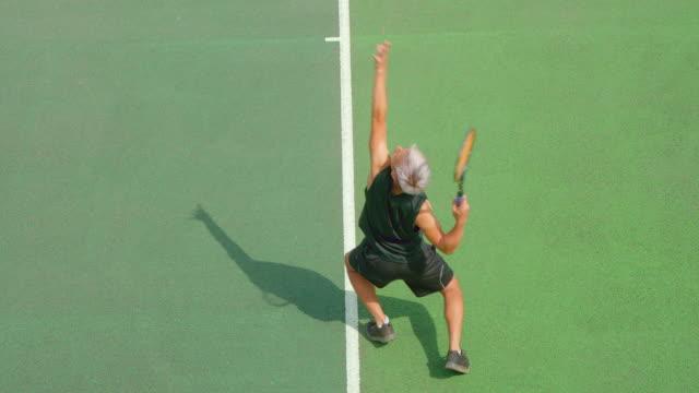 Ein junger Mixed-Renn-Tennisspieler dient. – Video