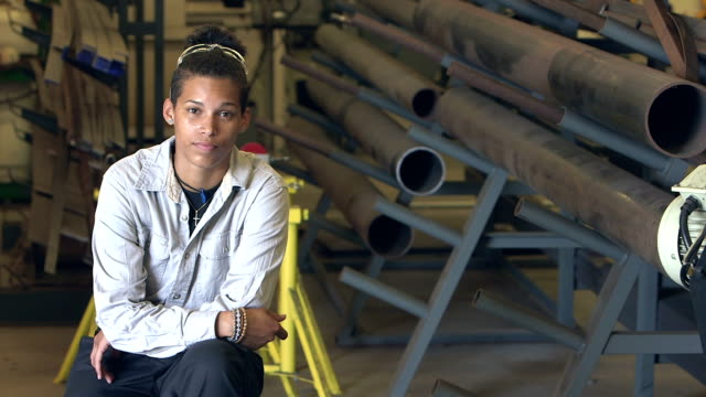 Young mixed race woman in a factory warehouse video