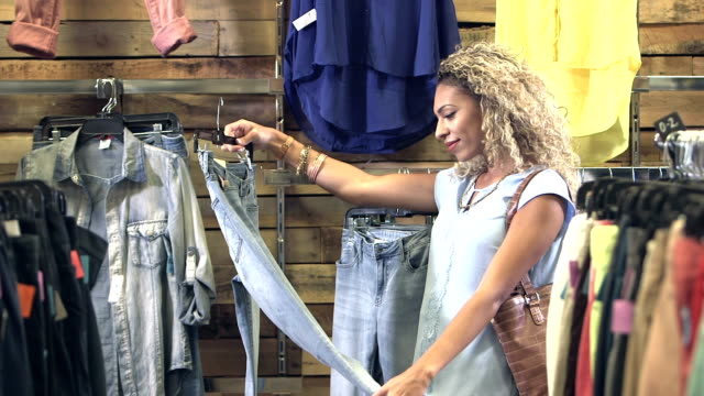 young mixed race woman shopping in clothing store - jeans video stock e b–roll