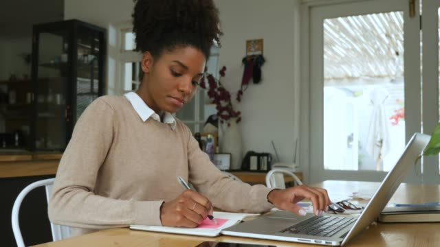 young mixed race woman with afro working from home in front of laptop - to do list video stock e b–roll