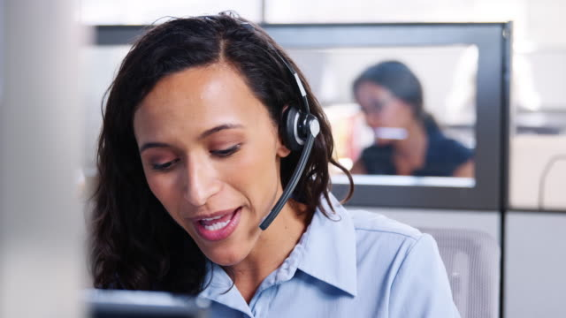 Young mixed race woman working in a call centre Young mixed race woman working in a call centre call centre videos stock videos & royalty-free footage