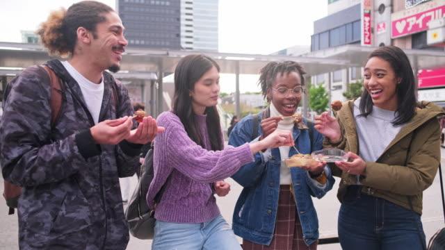 stockvideo's en b-roll-footage met jonge gemengde-etnische groep genieten van outdoor snack in tokio - vier personen