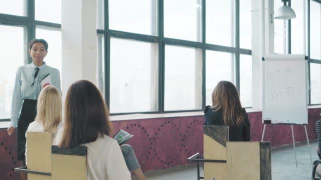 Junge Mixed-Race-Geschäftsfrau beendete die Präsentation, geht zu ihrem Sitz und sitzt auf einem Stuhl. Kreative Büro-Interieur. Co-Working Startup Team. Büroangestellte – Video