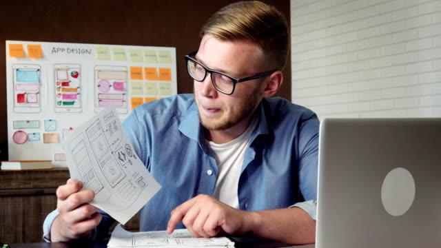 junge mobile app entwickler zeigen anwendungsprototyp an seinen klienten mit video-konferenz - reisebüro stock-videos und b-roll-filmmaterial