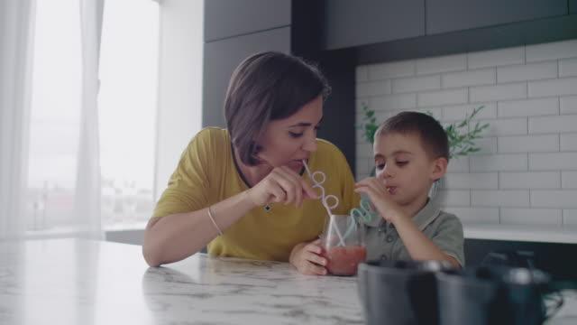ung mamma och son dricker saft med godis i köket. lycklig mamma spenderar tid med sonen sitter på bordet i slow motion. - cosy pillows mother child bildbanksvideor och videomaterial från bakom kulisserna