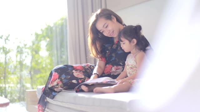 vídeos de stock, filmes e b-roll de jovem mãe lendo um livro a sua menina - ásia