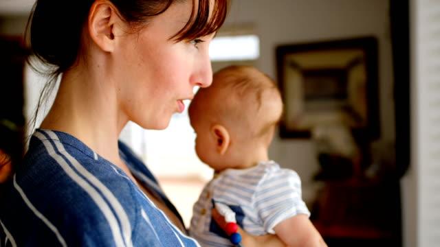 vídeos de stock, filmes e b-roll de jovem mãe em pé perto de janela enquanto exploração bebê 4k - bico