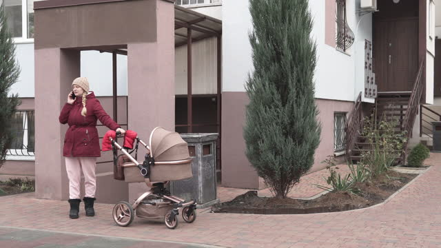 Young mom walks outdoors with a stroller and talking to her friends on the phone. Family, paternity concept - happy mother with stroller in the park. video