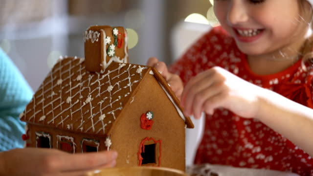 vídeos de stock e filmes b-roll de young mother and adorable daughter in red hat building gingerbread house together - christmas cookies