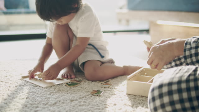 young mother and baby boy building a puzzle - puzzle video stock e b–roll