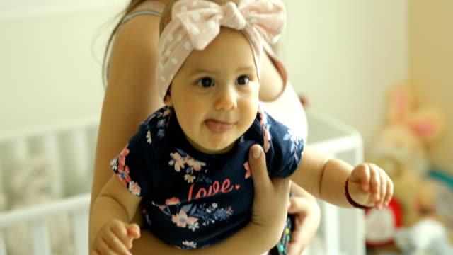 young mother and baby daughter at home - abbigliamento da neonato video stock e b–roll