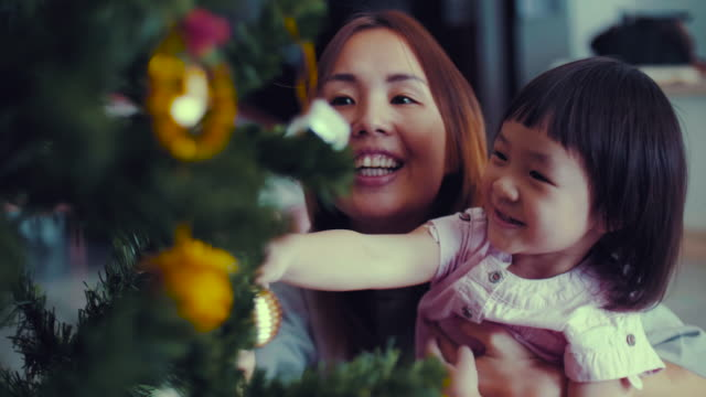 vídeos de stock e filmes b-roll de young mother and baby girl decorating christmas tree with ornaments - feriado