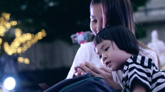 Young Mother And Baby Girl Using Smart Phone And Enjoyment In Christmas Festival video